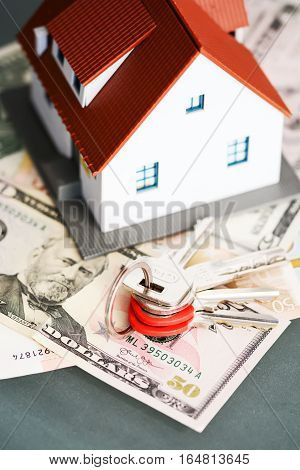 Buying a house concept with model house sitting on top of dollar bills and keys