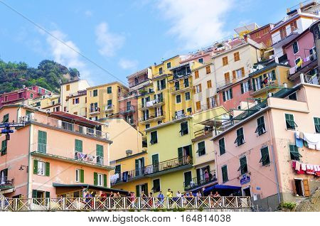 MANAROLA TOWN, RIOMAGGIORE, LA SPEZIA, LIGURIA, NORTHERN ITALY - 9 August, 2015:  View of the colourful houses on surrounding hills balconies and windows. Part of the Cinque Terre National Park and a UNESCO World Heritage Site.