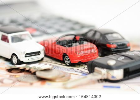 Buying or renting a car concept with car toys, car key, coins and bills
