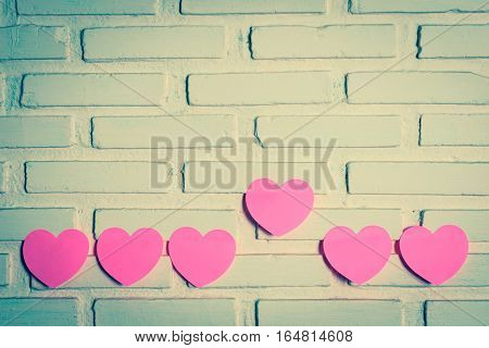 Pink sticky notes hearts shaped lined holes on the wall and a heart the outstanding one. vintage style