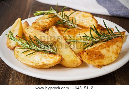 Roasted rosemary garlic potatoes. Baked golden crispy potato wedges on white plate on wooden background selective focus
