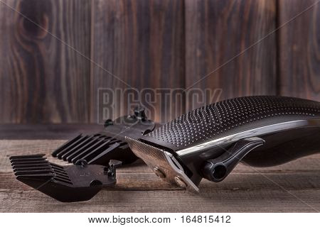 hair trimmer on an old wooden background closeup.