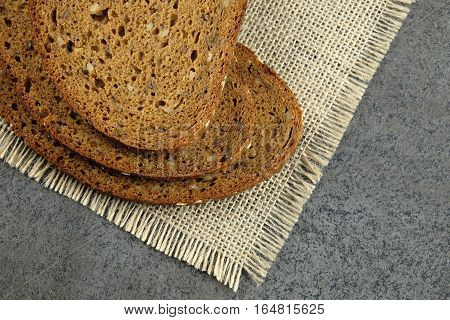 Three slices of grain bread on burlap cloth with dark background.