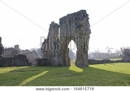 Ruined castle arch, archway with green field and summer weather Europe