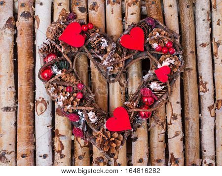 Decorative wreath in the shape of heart from cones twigs on wooden bars