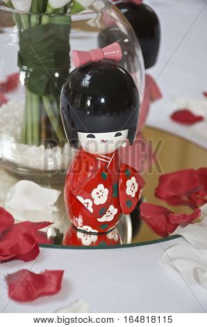 Japanese kokeshi doll, made of wood and is one of the most famous Japanese dolls and toys on a white table with petals