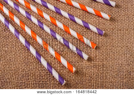 Colorful drinking striped straws on the background of burlap.