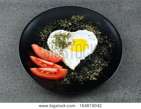 Fried egg in a shape of heart with herbs and tomatoes on a black plate with dark background.