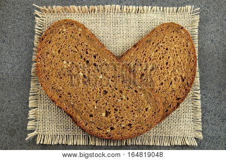 Two slices of grain bread in the shape of heart on a burlap cloth with a dark background.