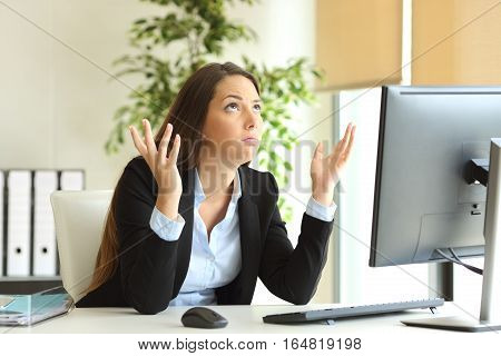 Worried businesswoman working online and praying looking above at office