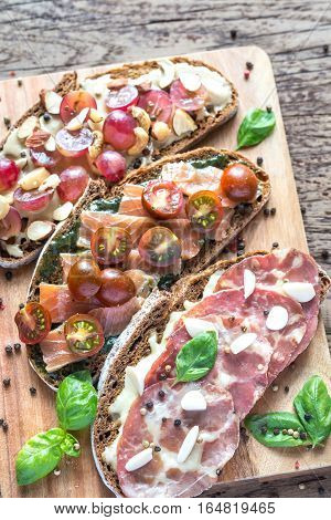 Bruschetta with different toppings on the wooden board