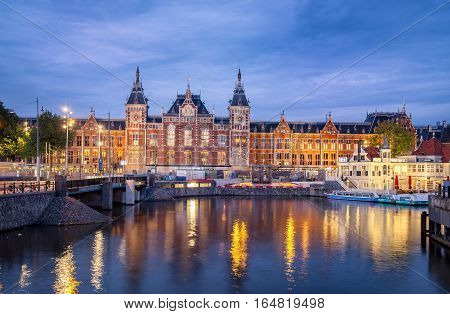 Central station on the banks of Amstel river in Amsterdam Netherlands.