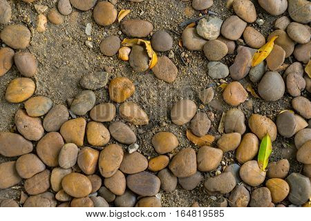 Round stones on sandy ground floor texture background.