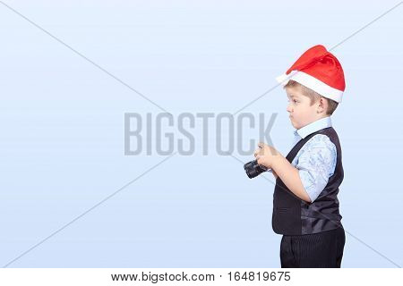 In cap of Santa Claus a little boy photographer