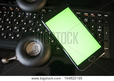 Laptop and headphones smartphone with green screen for key chroma screen.