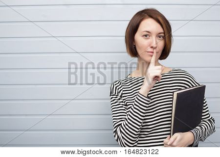 Female student with book standing near a wooden wall and puts her index finger to lips