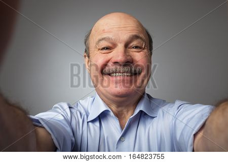 Elderly man with a mustache holding a smartphone and makes selfie smiling broadly