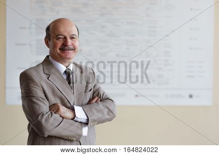 elderly man on blurry background of the poster folded his arms across his chest and looking confidently forward