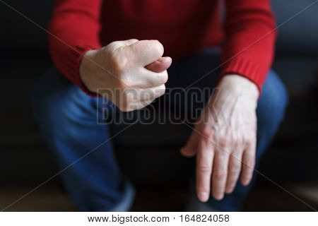 Man shows a fig from the fingers, sitting in a chair. Deny or refuse to do something