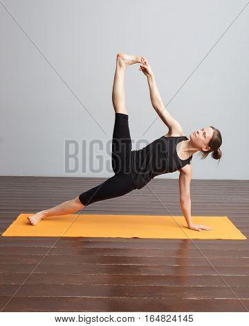 Vasisthasana. Girl doing side plank. On the pendant is written yogic symbol Aum