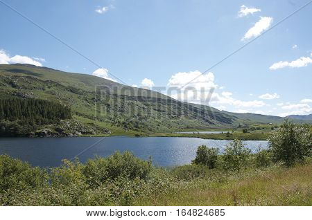 Capel Curig Lake Snowdonia in North Wales surrounded by hills, blue sky and forest