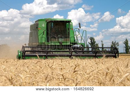 Kharkiv Ukraine - July 12 2011: Combine harvests wheat on a field in sunny summer day in Kharkiv Oblast Ukraine on July 12 2011