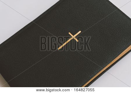 Catholic book with a gold cross, a Catholic book with gold pages and symbols. Catholic faith in Jesus Christ