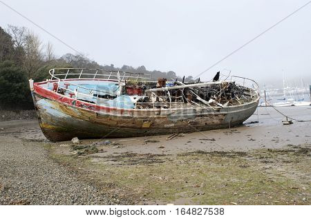 Burnt out ship wreck, boat fire damage, beached on coast shore line, fishing motor boat
