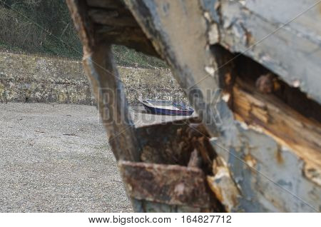Old wooden rowing boat beached, white and blue framed by wooden wreckage