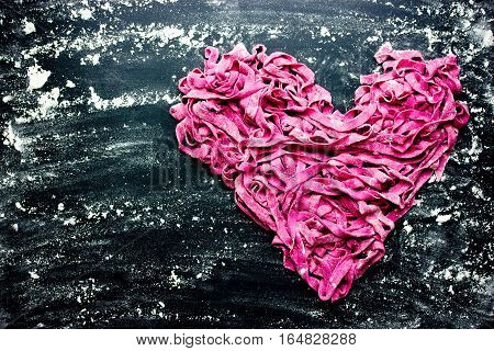 Fresh homemade beet pasta tagliatelle shaped heart on black background with flour