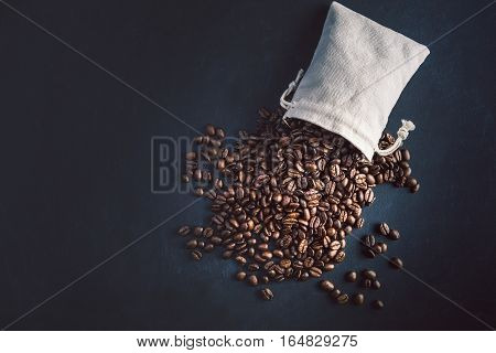 Coffee beans out of cloth bag with blue black textured background. Overhead conceptual photo with key accent lighting.