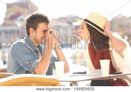 Side view of a tourist joking and photographing his girlfriend in a hotel terrace during summer holidays