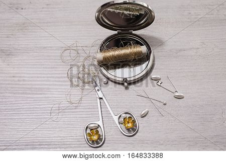 double mirror nail clippers golden thread pins needles and sewing items white beads on a light wooden background work of seamstresses