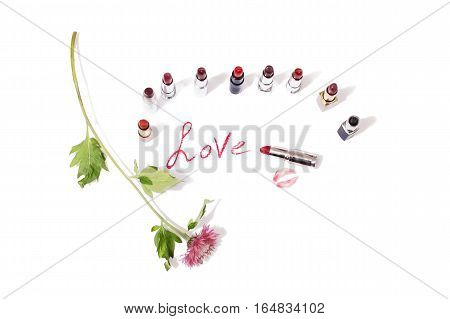 Multicolored glossy lipstick on an isolated background. Wild purple flower on a white surface. lips kiss on paper. The imprint of a red labial pencil. Cosmetic products for painting. The word love written in lipstick on a light surface. View from above