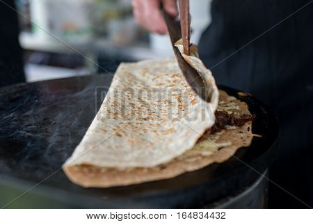 Folding A Crepe With Cheese And Onion Filling