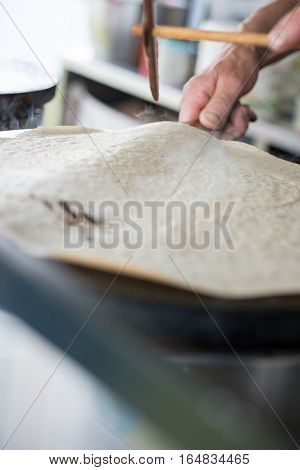 Crepe Batter On Hot Griddle About To Be Flipped Over