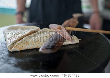 Folded Crepe On Griddle Pressed With Wooden Tools
