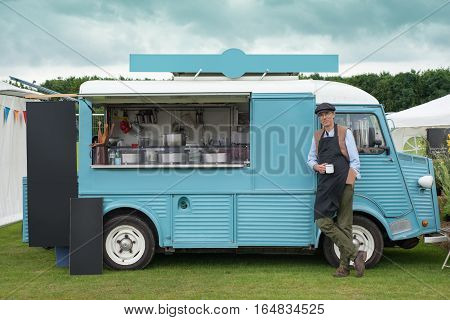 Man Standing By A Blue Food Truck