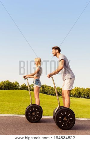 Young Cheerful Friends Driving Segways And Having Fun