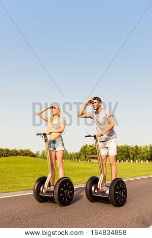 Happy Man And Woman Riding Segway And Looking For Way