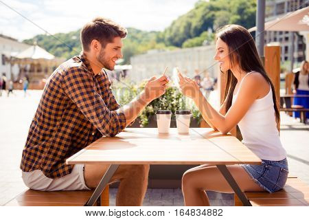 Two Lovers Having Date In Cafe And Typing Sms On Smartphones