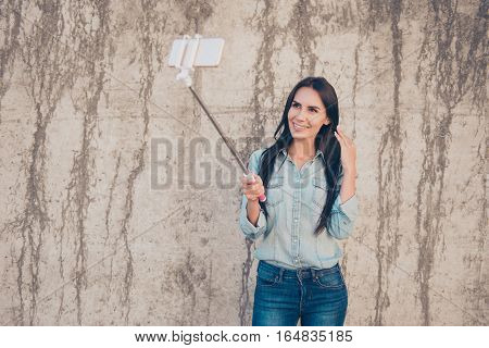 Attractive Girl Making Selfie With Monopod Near Stone Wall
