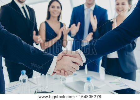 Close Up Of Two Business Partners Shaking Hands On Meeting