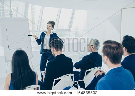 Group Of Employees Discussing Ideas During Presentation Of New Project At Briefing