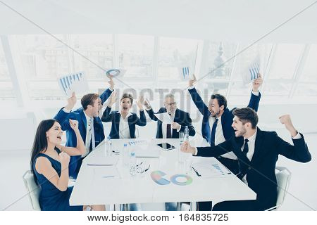 Happy Successful Businesspeople Triumphing With Raised Hands At Conference