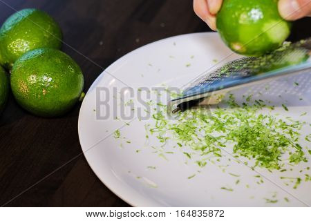 Grinding lime zest on to the white plane on the table