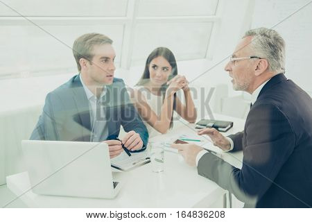 Portrait Of Concentrated Business People Discussing Paperwork In Office