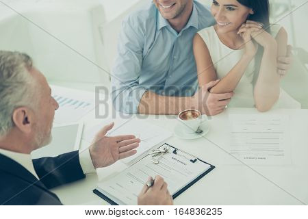 Close Up Of Real Estate Agent Giving Consultation To Family Couple