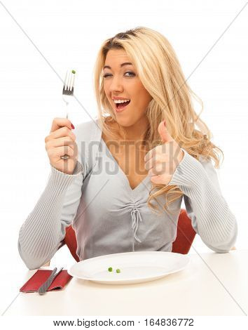 young blond woman enjoying a sumptuous meal of 3 whole green peas.