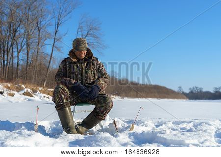 One euriopean man is fishing close to ice hole at winter sunny day under blue sky with forest at background